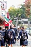 Japanese school girls heading towards the main torii gate at Fushimi Inari Taisha Shrine royalty free stock image
