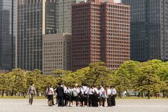 Japanese school group visiting the Imperial Palace in Tokyo with the skyscrapers of Chiyoda, Japan in the background stock images