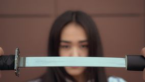Japanese schoolgirl pulls katana from scabbard with serious face. Confidend lady