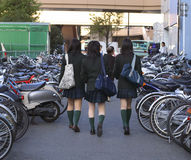 Japanese schoolgirls. Group of three Japanese schoolgirls walking between two rows of bicycles in a city street Stock Images