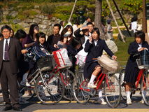 Japanese schoolgirls riding to school. Japanese schoolgirls on bikes waiting at a crossing at himeji Stock Image