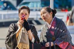 Japanese Senior women. TOKYO, JAPAN - NOVEMBER 26: Senior women in Tokyo, Japan on November 26, 2013. Unidentified Japanese women use a small compact camera royalty free stock photos