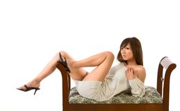 Japanese sensual leggy glamour. Glamorous Asian teenager lying down on fancy bench demonstrating her great legs Stock Photos