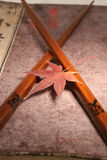 Japanese set. Old Japanese book from meiji period with chopsticks and japanese maple leaf stock image