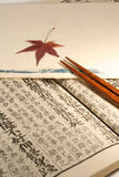 Japanese set. Old Japanese book from meiji period with chopsticks and japanese maple leaf stock photos