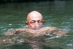 Japanese bald head guy emerging from water Royalty Free Stock Image