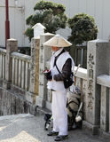 Japanese Shinto monk stand for alms Stock Images
