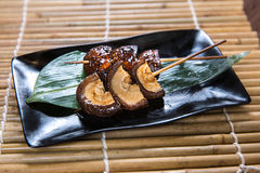Japanese Shitake Mushroom Kushiyaki, Skewered and Grilled Meat. 2 pieces grilled skewered shitake mushroom on a plate Stock Photos