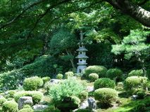 A Japanese shrine in a formal garden. A Japanese stone shrine in a typical formal garden. It is surrounded by small pruned green shrubs and rocks. An old tree royalty free stock image