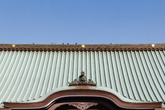 Japanese shrine`s rooftop. Closeup Japanese shrine`s rooftop with visible frontal bronze artwork stock photos