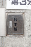Japanese sign of water tap of hydrant fireplug. On the concrete wall Royalty Free Stock Images