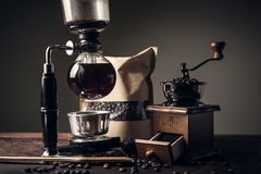 Japanese siphon coffee maker and coffee grinder. On old kitchen table Royalty Free Stock Photography