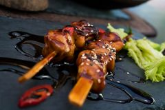 Yakitori, Saucy Skewer. A Japanese skewered chicken dish called Yakitori, with a salad leaf and sauce Stock Images