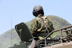 Japanese soldier with military tank. KAGAWA, JAPAN - APRIL 23 2017: Japanese soldier in the armored vehicle going to the Zentuji military base Stock Photos