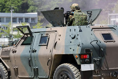 Japanese soldier with military tank. KAGAWA, JAPAN - APRIL 23 2017: Japanese soldier in the armored vehicle going to the Zentuji military base Stock Photography