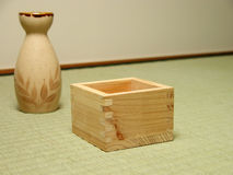 Japanese still life. A wooden sake cup and a sake bottle on a tatami floor.Selective focus on the cup edge Royalty Free Stock Images