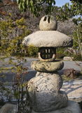 Japanese stone lantern. With cherries in bloom in the background in Mount Koya, Japan Royalty Free Stock Photography