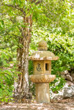 "Japanese Stone Lantern Marker. An Oribe Lantern with ancient Asian writing, which can translate as ""crawling,"" stands next to a beautiful tree.  Beads of Stock Photography"