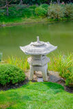 Japanese stone lantern by pond Stock Image