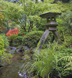 Japanese Stone Lantern by Water Stream Royalty Free Stock Photos