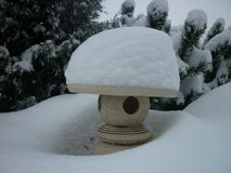 Japanese stone lantern. Winter landscape, Japanese stone lantern in the garden, covered with snow,  on the background of spruce Stock Photography