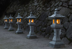 Japanese stone lanterns in the evening. Traditional japanese stone lanterns burning in the evening Stock Photo