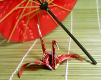 Japanese story. A paper Japanese figurine and Japanese umbrella suggestion on a bamboo floor Stock Photo