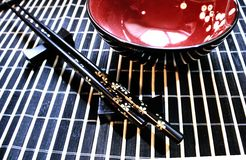 Japanese style. Red sake and rice cup, chopsticks on holder on bamboo mat Stock Photography