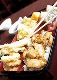 Japanese Style Bento Box. A traditional bento box as it would be eaten in japan, with chicken teriyaki, tempura, salad and rolls Stock Photography