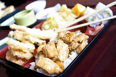 Japanese Style Bento Box. A traditional bento box as it would be eaten in japan, with chicken teriyaki, tempura, salad and rolls Stock Photo