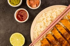 Japanese Style Breaded Chicken Katsu Curry With Boiled Sushi Ric. E On A Black Tiled Background Royalty Free Stock Images