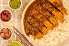 Japanese Style Breaded Chicken Katsu Curry With Boiled Sushi Ric. E On A tiled Kitchen Tabletop Counter or Worktop Royalty Free Stock Photo