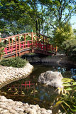 Japanese style bridge over pond Stock Photography