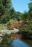 Japanese style bridge over pond Royalty Free Stock Photo