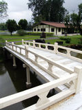 Japanese style building and bridge. An image of traditional classical japanese landscaping, with a low white wooden bridge in the foreground over a river or pond stock images