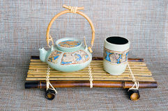 Japanese style ceramic teapot and cup. On the bamboo stand Stock Photography