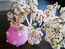 Japanese style decoration cherry flowers. Japanese style decoration - pink ball and beautiful artificial cherry flowers royalty free stock image