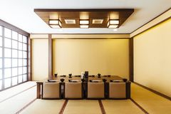 Japanese style dining room with wooden table in the center and eight cushion seats decorated in earth tone.  royalty free stock images