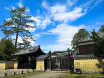 Japanese style house kiosk, roof, fence, gate with dark green tr Stock Images