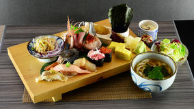 Japanese style raw fish sashimi sushi plate. Japanese style raw fish sashimi and sushi on plate with scallop and many raw fishes and tofu egg dessert and some Royalty Free Stock Images