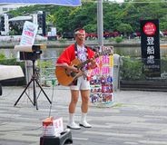 Japanese Style Street Musician. KAOHSIUNG, TAIWAN -- JUNE 9, 2016: A male busker wearing Japanese clothes performs popular Japanese songs on the banks of the Stock Photo