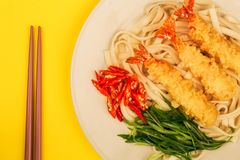 Japanese Style Tempura Prawns With Udon Noodles Chilli and Spring Onions. Against A Yellow Background stock image
