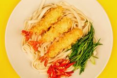 Japanese Style Tempura Prawns With Udon Noodles Chilli and Spring Onions. Against A Yellow Background stock photography