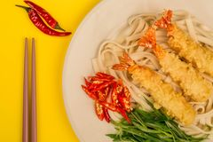 Japanese Style Tempura Prawns With Udon Noodles Chilli and Spring Onions. Against A Yellow Background stock images