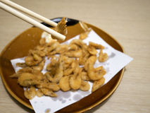 Japanese styled fried shrimps. The front focus photo of  japanese styled fried shrimps in the brown ceramic plate and chopsticks Stock Images