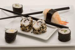 Japanese sushi with chopsticks. On a white plate stock photography