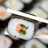 Japanese Sushi on chopsticks Stock Photos