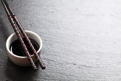 Japanese sushi chopsticks over soy sauce bowl Royalty Free Stock Images