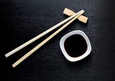 Japanese sushi chopsticks over soy sauce bowl, rice on black bac Stock Images