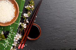 Japanese sushi chopsticks over soy sauce bowl, rice and sakura b Stock Photos